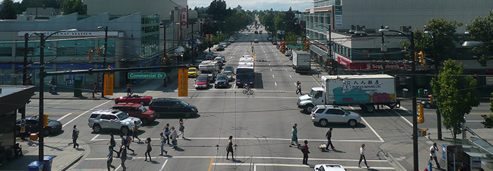 People walking on a crosswalk and vehicles at the Commercial Drive and Broadway intersection