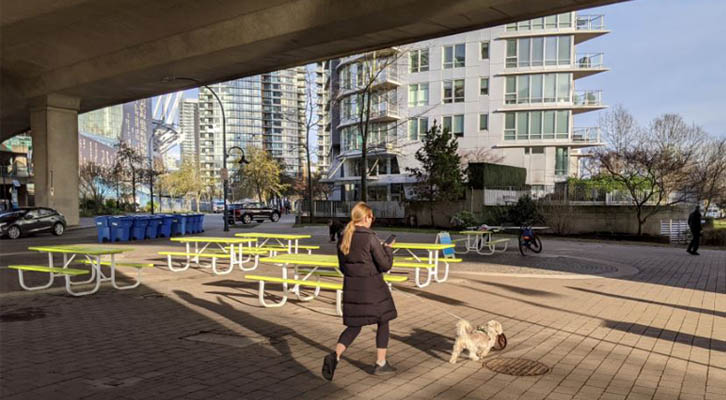 Person walking dog under a covered pop-up patio