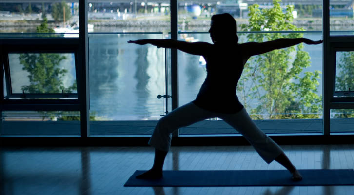 Person in the yoga warrior pose at Creekside Community Centre with False Creek in the background