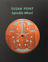 Book cover image of a red, flat circle of wood with Indigenous animal shapes carved into it