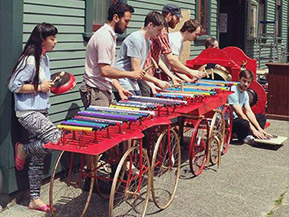 Six musicians from Publik Secrets play a long colourful xylophone