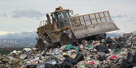 A bulldozer drives over a large mound of garbage at the Vancouver Landfill with the North Shore Mountains in the background on a cloudy day