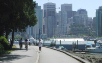 Runners and cyclists on the seawall with downtown Vancouver in the background