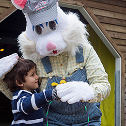 Easter Bunny waves while getting a hug from a young girl at the Stanley Park Easter Train