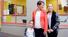 BC Minister Melanie Mark stands smiling with a girl and young women in front of her office on Commercial Drive, Vancouver.