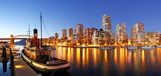 A cityscape of Vancouver at night with boats and bridges.