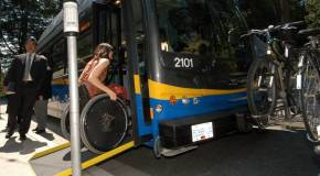 Woman in a wheelchair boarding a bus using ramp