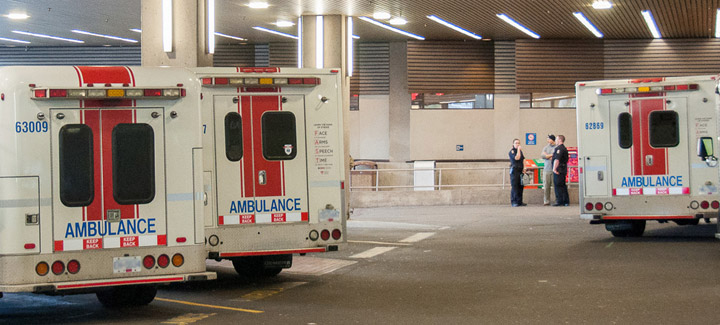 Three ambulances parked at VGH Emergency with paramedics in the background