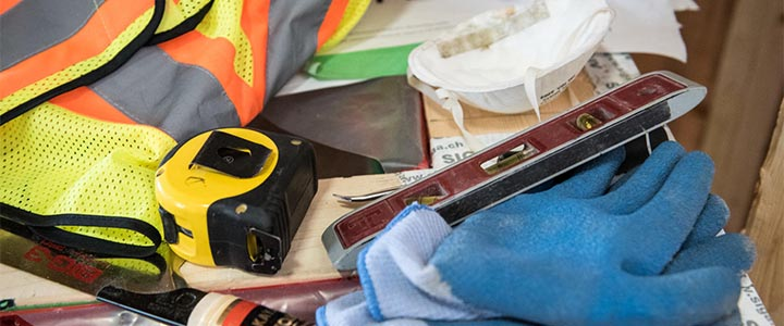Construction tools - gloves, mask, safety, vest, tape measure, and leveler sitting on a table