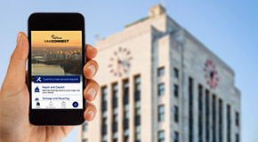 Person using the City of Vancouver VanConnect app on their mobile phone with City Hall in the background