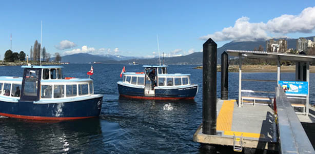 Two ferries in water approaching ferry dock