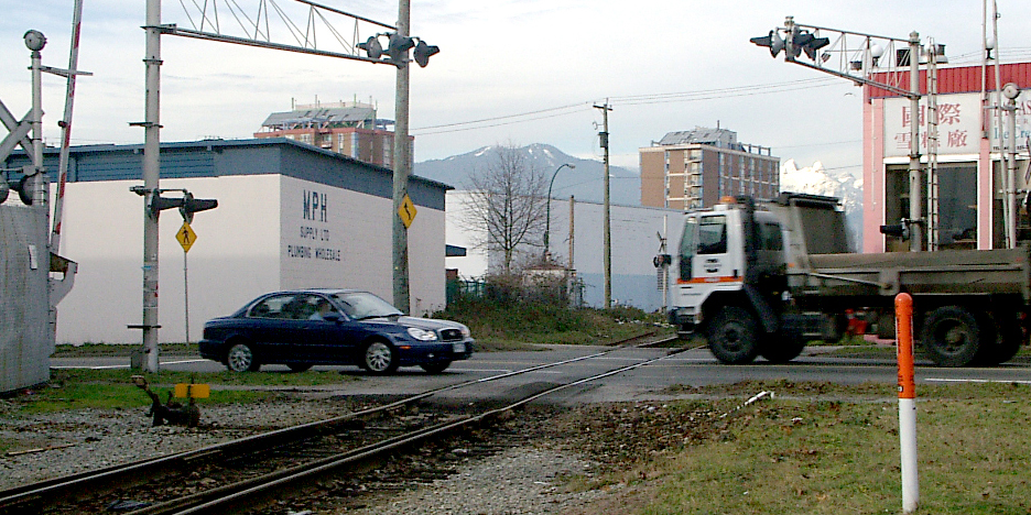 Two vehicles crossing train tracks