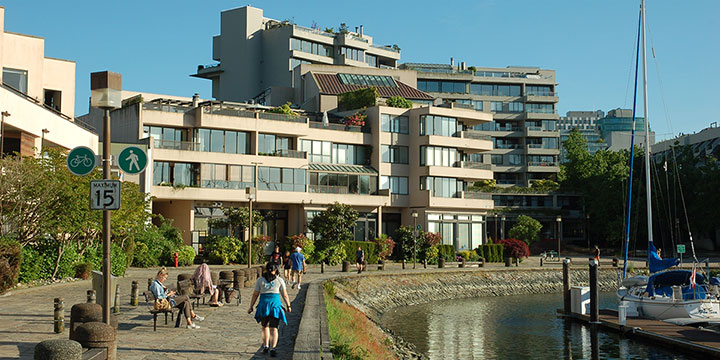 People walking along Millbank and the Seawall in False Creek South with strata leasehold housing on City-owned land in the background