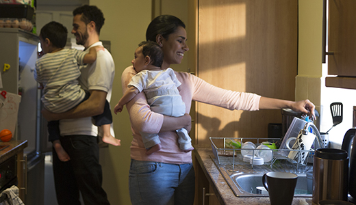 Mom holds baby at kitchen sink while dad holding toddler looks in fridge