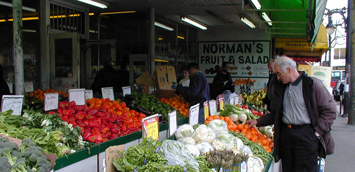 Man looking at oranges at fruit and vegetable stand