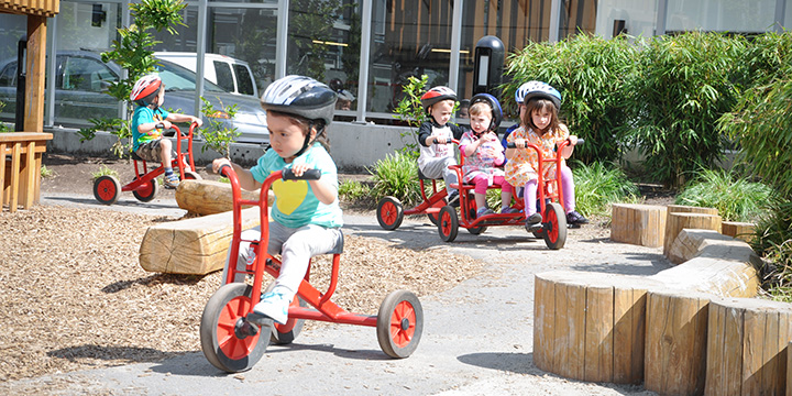 Children riding tricycles by a childcare playground