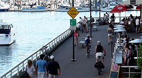 People walking and cycling along the Seawall on the north side of False Creek