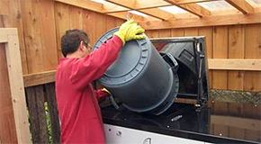 Man emptying a container into an on-site composting system