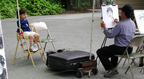 A girl poses for a portrait artist in Stanley Park