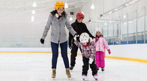 Parents skating with their kids at an ice rink