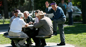 A group of senior men enjoying a board game in a city park