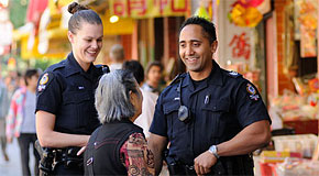 An senior woman speaks with two Vancouver Police officers on patrol in Chinatown