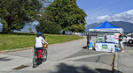 Cyclist in Stanley Park approaching a Park Board engagement booth