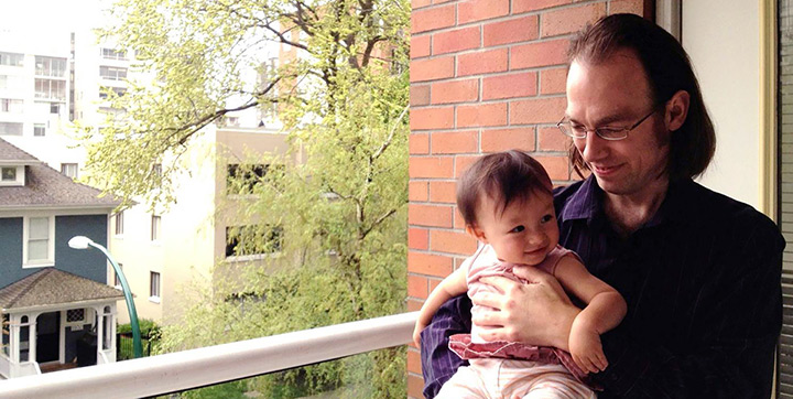 Father holding their baby on an apartment balcony in Vancouver