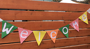 A welcome banner hung on a fence