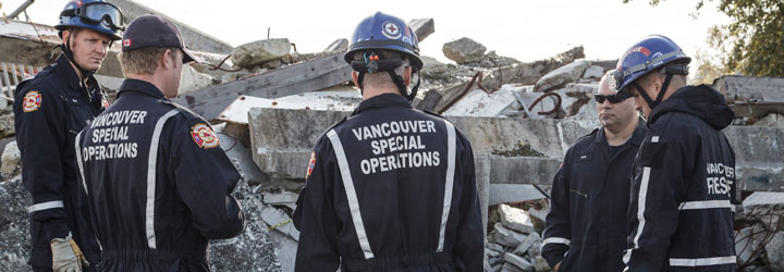 A group of Vancouver Fire and Rescue Services Special Operations members with hardhats in front of concrete rubble