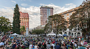 People gathered at Victory Square to watch a music concert, with heritage buildings along Hastings Street in the background