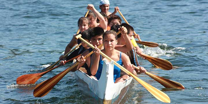 Indigenous youth paddling in the Coast Salish Canoe Races