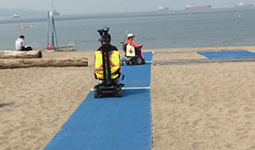 Two people using wheelchairs on a beach mat