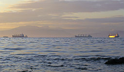 Cargo ships on water at sunset