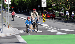 Father and young son cycling on the Comox-Helmcken Greenway.