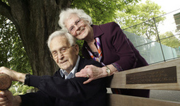 Older woman hugs her husband sitting on a park bench