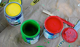 Photo of open yellow, green, and red paint cans