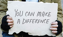Person who is homeless holding a cardboard sign that reads 'you can make a difference'