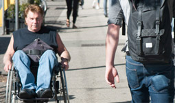 Man in wheelchair rolling on the sidewalk down Commercial Drive