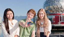 A red-haired teenage boy holds a Vancouver Public Library card with a brunette girl and blonde girl by his side, with Telus World of Science in the background