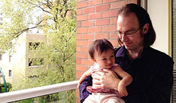 Parent holding their baby on an apartment balcony in Vancouver