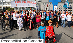 A crowd of people walking in the 2017 Walk for Reconciliation on the Georgia Viaduct, some holding a banner reading 'A new way forward', some waving flags, some wearing Reconciliation Canada t-shirts, with First Nations elders and children in regalia