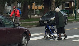 Car and cyclist stop at crosswalk as woman walks across street at crosswalk