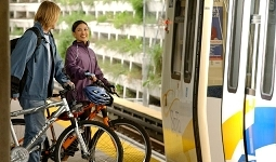 Two people with bikes going onto the SkyTrain