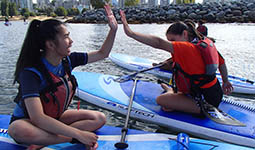Two youth high-fiving while sitting on paddleboards